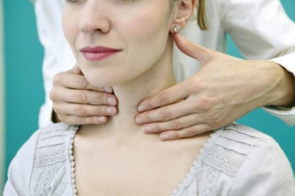 женщине щупают щитовидку